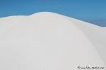 Schneeweiße Sanddünen vor blauer Kulisse
