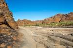 Ausgewaschenes Flussbett gesäumt von den Felsmassiven mit den Bienenkörben
