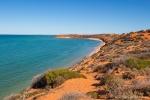 Roter Sandstrand trifft auf türkisblaues Meer