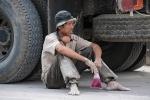 Pause im Schatten - als Atemschutzmaske dient ein altes Stück Schaumgummi und das Trinken kommt aus der Plastiktüte
