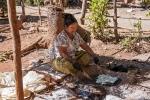 Herstellung von Reiscrackern in Tha Kaung - in heißem Sand werden die getrockneten Reisfladen ausgebacken