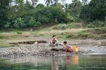 Die Frauen sammeln Kies aus dem Flussbett, um ihn zu verkaufen