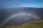 Der aufziehende Nebel formt sich zu einem Regenbogen über dem Kraterrand des