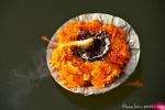 Blumenschälchen mit brennendem Docht treiben im Ganges